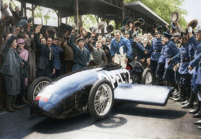 Jos pălăria: Fritz von Opel fericit după cursa nebună cu RAK 2. Opel a retușat originala fotografie alb negru din 1928 pe baza informațiilor istorice pentru a aniversa 90 de ani de la cursa de doborâre a recordului de viteză.
